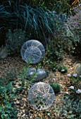 ALUMINIUM GLOBES STANDING ON GRAVEL AND SURROUNDED BY GREY GRASSES  CONVULULUS CNEORUM AND LOBELIA SIPHILITICA . ROBIN GREEN AND RALPH CADES SEASIDE STYLE GARDEN  LONDON