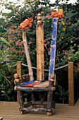 A PLACE TO SIT: AN ASTROLOGICAL THRONE MADE FROM RECYCLED WOOD & ROUGHLY PAINTED. AT THE TOP IS A CARVED CRAB & LION. ROBIN GREEN AND RALPH CADES SEASIDE STYLE GARDEN  LONDON