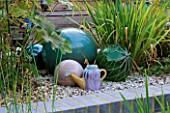 TURQUOISE CERAMIC BALLS  FISHING FLOATS AND A SPANISH CERAMIC WATERING CAN STAND ON GRAVEL. ROBIN GREEN AND RALPH CADES SEASIDE STYLE GARDEN  LONDON