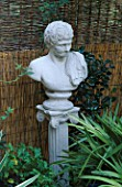 A CLASSICAL BUST MOUNTED ON A COLUMN CREATES A FOCAL POINT IN FRONT OF A SPLIT BAMBOO AND WOVEN WICKER FENCE. ROBIN GREEN & RALPH CADES SEASIDE STYLE GARDEN  LONDON