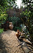 VIEW ACROSS SHINGLE & STEPS LINED WITH SLEEPERS TO THE WICKER AND BAMBOO FENCE. WITH TERRACOTTA URNS & PHORMIUM ATROPURPUREUM. ROBIN GREEN & RALPH CADES SEASIDE STYLE GDN  LONDON.
