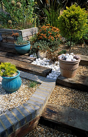 VIEW_ACROSS_THE_SHINGLE_GARDEN_TOWARDS_THE_WOODEN_HERB_SEAT_WITH_SLEEPERS_ACTING_AS_STEPS__TOPIARY__