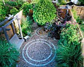 SMALL GARDEN WITH CIRCULAR BRICK PATTENS IN GRAVEL. WITH NATURAL WOODEN SWING SEAT AND STOOL  VERBENA BONARIENSIS AND CLEMATIS. BAMBOO FENCING CREATES AN ATTRACTIVE BORDER.