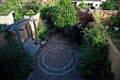 OVERVIEW OF SMALL GARDEN WITH CIRCULAR BRICK PATTENS IN GRAVEL. NATURAL WOODEN SWING SEAT AND STOOL  VERBENA BONARIENSIS & CLEMATIS. BAMBOO FENCING CREATES AN ATTRACTIVE BORDER.
