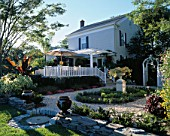 VIEW ACROSS GARDEN TOWARDS WHITE HOUSE WITH VERANDAH  CANVAS PARASOL AND URNS ON DRY STONE WALL.  BILL SMITH AND DENNIS SCHRADERS GARDEN  LONG ISLAND  USA