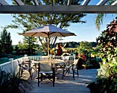 VIEW ACROSS DECKED VERANDAH WITH SIX CANVAS CHAIRS AND PARASOL. BILL SMITH AND DENNIS SCHRADERS GARDEN  LONG ISLAND  USA