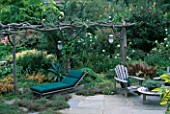 UNUSUAL PERGOLA MADE FROM NATURAL TIMBER STANDS OVER GREEN CANVAS SUN LOUNGER AND WOODEN GARDEN FURNITURE. BILL SMITH AND DENNIS SCHRADERS GARDEN  LONG ISLAND  USA
