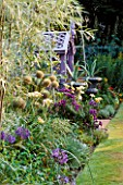 MAUVE WOODEN SEATWITH SILVER PAINTED METAL URNS PLANTED WITH AGAVES. IN BORDER ARE ALLIUM GIGANTEUM  HEMEROCALLIS LUXURY LACE AND ERIGERON AZURE FAIRY. NICHOLS GARDEN  READING