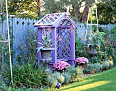 NICHOLS GARDEN: COVERED WOODEN SEAT SURROUNDED BY SILVER PAINTED METAL STANDS AND TWO URNS PLANTED WITH AGAVES. IN TWO POTS ARE PINK CHRYSANTHEMUMS. NICHOLS GARDEN  READING