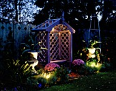 NICHOLS GARDEN: COVERED WOODEN SEAT SURROUNDED BY TWO SILVER PAINTED METAL URNS PLANTED WITH AGAVES. IN TWO POTS ARE PINK CHRYSANTHEMUMS. LIGHTING BY GARDEN & SECURITY LIGHTING