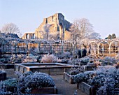 FROZEN POND CREATES A FOCAL POINT FOR THE HERB GARDEN WITH FROSTED WIGWAMS  THE CIRCULAR ARCADED WALK & RUINED ABBEY IN THE BACKGROUND. THE ABBEY HOUSE  WILTSHIRE. (SAME AS 20132)