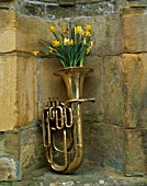 BRONZE TUBA FILLED WITH NARCISSUS TETE-A-TETE  MIDGET AND HAWERA. DESIGNED BY IVAN HICKS. GROOMBRIDGE PLACE  KENT.