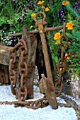 RUSTY ANCHOR NEXT TO DRIFTWOOD BENCH WITH PATTERNED GRAVEL FLOOR  VIOLAS & MARIGOLDS.  WARREN FARM CENTRES THE ESSENCE OF LIFE  GARDEN. DES: ROSAMOND PAGE  CHELSEA 2000