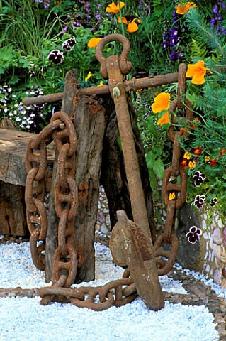 RUSTY_ANCHOR_NEXT_TO_DRIFTWOOD_BENCH_WITH_PATTERNED_GRAVEL_FLOOR__VIOLAS__MARIGOLDS__WARREN_FARM_CEN