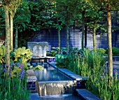 ROWS OF PLEACHED LIMES ALONG A WATER RILL WITH IRISES AND BLUE GLAZED BRICK WALLS. CARTIERS A CITY SPACE GARDEN DESIGNED BY MARK WALKER. CHELSEA 2000