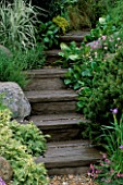 MAN MADE STEPS MADE TO LOOK LIKE WOODEN SLEEPERS  LINED WITH GRASSES & AJUGA. STONEMARKETS A WATERSIDE RETREAT DESIGNED BY GEOFFREY WHITEN. CHELSEA 2000