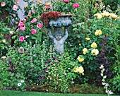 CAROLYN HUBBLES SHROPSHIRE GARDEN. BRONZE STATUE WITH ENGLISH ROSE REDOUTE  ROSA MAGENTA AND ROSA CHARLOTTE