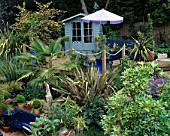 SLOPING BACK GARDEN WITH UPPER DECK OF DECKING WITH ROPE EDGING  BLUE SUMMERHOUSE  PHORMIUM  TRACHYCARPUS FORTUNEI AND PARASOL. ROBIN GREEN & RALPH CADES GARDEN  LONDON