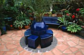 SOFT TERRACOTTA CRAZY PAVING PATIO WITH BLUE CERAMIC SEATS AND TRACHYCARPUS FORTUNEI. ROBIN GREEN & RALPH CADES GARDEN  LONDON