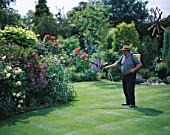 CAROLYN HUBBLES GARDEN  SHROPSHIRE: JOHN PRICE WATERING THE ROSES