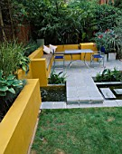 A PLACE TO SIT: ALUMINIUM TABLE AND CHAIRS ON PATIO SURROUNDED BY YELLOW RENDERED WALLS WITH RAISED BEDS AND RILL. OLEANDER IN GALVANISED CONTAINER. DESIGNER JOE SWIFT