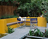 A PLACE TO SIT: ALUMINIUM TABLE AND CHAIRS ON PATIO SURROUNDED BY YELLOW RENDERED WALLS WITH RAISED BEDS AND RILL. TRACHYCARPUS AND PHORMIUM FOLIAGE IN B/G . DESIGNER JOE SWIFT