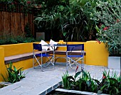 A PLACE TO SIT: ALUMINIUM TABLE AND CHAIRS ON PATIO SURROUNDED BY YELLOW RENDERED WALLS WITH RAISED BEDS AND OLEANDER   TRACHYCARPUS. DESIGNER JOE SWIFT