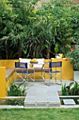 A PLACE TO SIT: ALUMINIUM TABLE AND CHAIRS ON PATIO SURROUNDED BY YELLOW RENDERED WALLS AND  RILL WITH OLEANDER   TRACHYCARPUS. DESIGNER JOE SWIFT