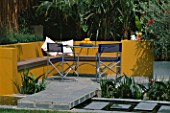 A PLACE TO SIT: ALUMINIUM TABLE AND CHAIRS ON PATIO SURROUNDED BY YELLOW RENDERED WALLS WITH RAISED BEDS AND RILL WITH OLEANDER   TRACHYCARPUS. DESIGNER JOE SWIFT
