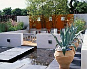 MINIMALIST GARDEN BY WYNNIATT-HUSEY CLARKE: CRETAN URNS WITH AGAVE AMERICANA  CONCRETE WALLS WATER  BLACK LIMESTONE STEPS  ORANGE PAINTED WALLS  GALVANISED METAL CONTAINERS.