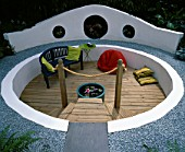 A CIRCULAR SUNKEN TIMBER DECK PATIO AREA WITH BEANBAG  GLAZED POT WITH WATERLILY AND BLUE SEAT. HAMPTON COURT 2000  DESIGNER BOARDMAN GELLY & CO