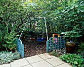 CHILDRENS SWINGS WITH BARK CHIP UNDERNEATH  BLUE TRELLIS  FIG (FICUS BROWN TURKEY)   FATSIA JAPONICA AND TERRACOTTA WATER FEATURE.