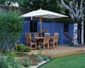 BLUE SUMMERHOUSE WITH DECKING  TABLE  CHAIRS AND PARASOL  BIRCH TREE TRUNKS  ORNAGE LILLIES  HAMMOCK AND GRAVEL. DESIGNER: CLARE MATTHEWS