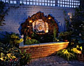 WATER FEATURE: RECTANGULAR BRICK POOL WITH SHELL WALL FOUNTAIN BACKED BY ROCK AND BRICK WALL PAINTED BLUE  LIT UP AT NIGHT. DESIGNER: ANDREW ANDERSON