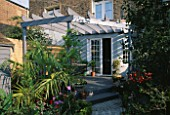 VIEW TO KITCHEN DOOR WITH DECKED TERRACE  PERGOLA  SHED  TRACHYCARPUS AND STONE SETT PATH.  DESIGNER: ANDREW ANDERSON