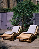 GARDEN WITH DECKING DESIGNED BY JOE SWIFT/ THAMASIN MARSH: WOODEN SUN LOUNGERS WITH LILAC/GREY FENCE AND SHED BEHIND