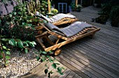 GARDEN WITH DECKING DESIGNED BY JOE SWIFT AND THAMASIN MARSH: WOODEN SUN LOUNGERS WITH LILAC/GREY FENCE AND SHELL MULCH
