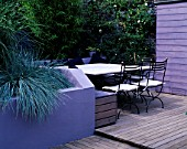 GARDEN WITH DECKING DESIGNED BY JOE SWIFT AND THAMASIN MARSH:  LILAC/GREY SHED AND RENDERED WALL OF RAISED BED WITH BLUE FESTUCAS  STONE TOPPED TABLE AND CHAIRS