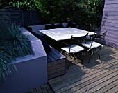 GARDEN WITH DECKING. DESIGN JOE SWIFT AND THAMASIN MARSH: LILAC/GREY RAISED BED WITH RENDERED WALL AND BLUE GRASSES.  STONE TOPPED TABLE  CHAIRS AND BENCHING WITH CUSHIONS.   SHED