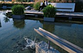 GALVANISED METAL SHUTE FORMS WATER SPOUT IN MINIMALIST WATER GARDEN DESIGNED BY ULF NORDFJELL.  HEDENS LUSTGARD  SWEDEN