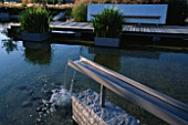GALVANISED METAL SHUTE FORMS WATER SPOUT IN MINIMALIST WATER GARDEN DESIGNED BY ULF NORDFJELL. FOLIAGE OF IRIS ENSATA IN GALVANISED CONTAINERS.  HEDENS LUSTGARD  SWEDEN