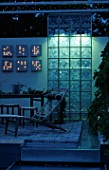 MODERN BALCONY GARDEN AT NIGHT: WOODEN SUNLOUNGER  FAIRY LIGHTING AND GLASS SCREEN WATER CASCADE. DESIGNER: NINA THALINSON OF LUST & FAGRING. HEDENS LUSTGARD  SWEDEN