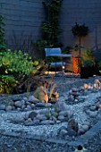 GARDEN AT NIGHT: REFLECTIVE GRAVEL RIVER RUNS AROUND COBBLES. METAL TABLE AND CHAIR IN B/G. DESIGNER: HEIDI PALMGREN. HEDENS LUSTGARD  SWEDEN