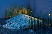 GLASS AND WATER GARDEN AT NIGHT. LIGHTING SHAFTS ACROSS CRUSHED GLASS MOUNDS INTERPLANTED WITH  TYPHA. DESIGNED BY S.L.U ALNARP. HEDENS LUSTGARD  SWEDEN