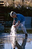 CHILD PLAYS IN FOUNTAIN IN MINIMALIST WATER GARDEN DESIGNED BY ULF NORDFJELL. HEDENS LUSTGARD  SWEDEN