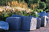 ANGULAR ROCKS SURROUND MINIMALIST GARDEN BY ULF NORDFJELL. PLANTING WITH LILUM REGALE AND DESCHAMPSIA CESPITOSA.  HEDENS LUSTGARD  SWEDEN