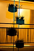 BACK-LIT BALCONY GARDEN AT NIGHT WITH TRANSPARENT PLASTIC RAILINGS AND MINIMAL TRELLIS WITH PLANT HOLDERS.  HEDENS LUSTGARD  SWEDEN.