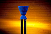 BACK-LIT BLUE URN BY MARIE KARUP SITS ON PEDESTAL  AT HEDENS LUSTGARD  SWEDEN