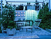 MODERN BALCONY GARDEN AT NIGHT: WOODEN SUNLOUNGER  FAIRY LIGHTING   GLASS SCREEN AND WHITE SWEET PEAS IN POT. DESIGNER: NINA THALINSON OF LUST & FAGRING. HEDENS LUSTGARD  SWEDEN
