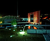 NIGHT TIME VIEW ACROSS MINIMALIST WATER GARDEN  DESIGNED BY ULF NORDFJELL.  DECKING  SCREEN AND WATER FEATURE.  HEDENS LUSTGARD  SWEDEN